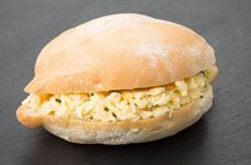 Large warm soft roll with scrambled egg and chives v